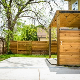 Solid wood privacy fence, surrounding a residential backyard with a concrete walkway leading in.