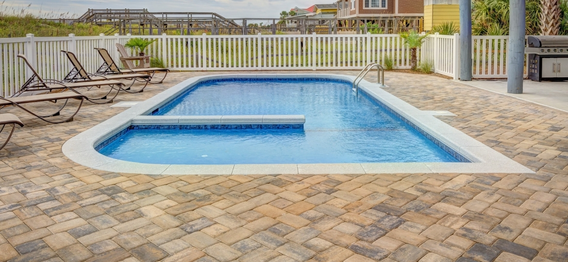 A stone paver patio with an in-ground pool. Lounge chairs line the left side of the patio. A white pool fence surrounds the area in a residential neighborhood as the background.