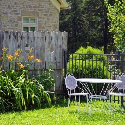 A white patio set sits on a grass patio. It is a sunny day. There are orange lilies lining a wooden fence in the background.