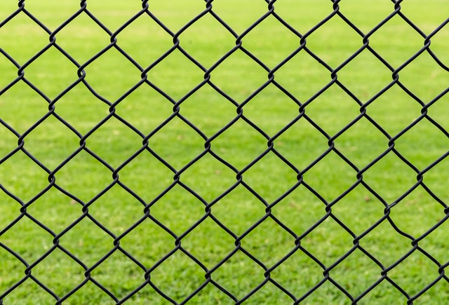 Close up of chain link fence with grass in the background.