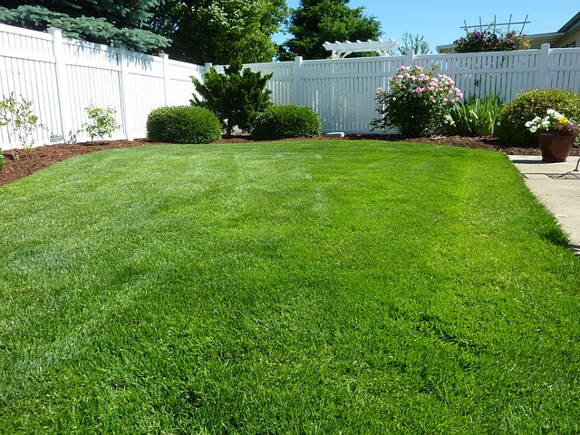 A white vinyl privacy fence surrounds a backyard of green grass and beautiful landscape.
