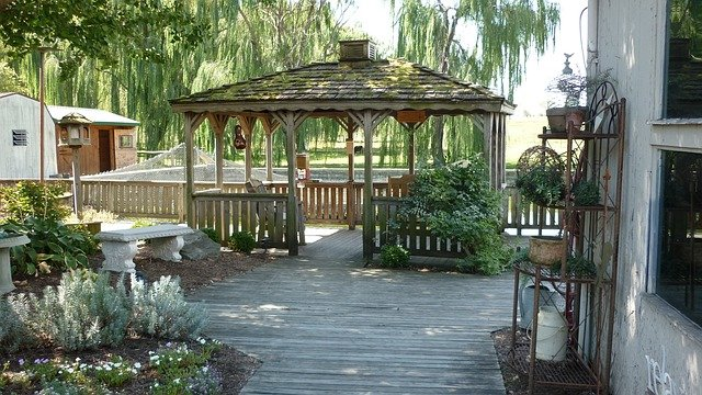 A wooden deck and gazebo with wood backyard fencing.