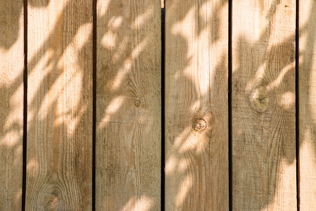 A new wooden fence, with a trees shadow on it.