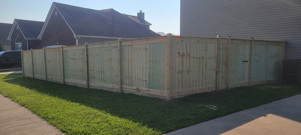 Wood fence after proper fence care, surrounded by green grass.