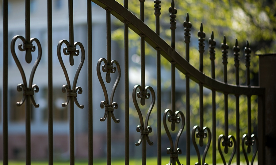 Black iron fence in the foreground and a green yard in the background.