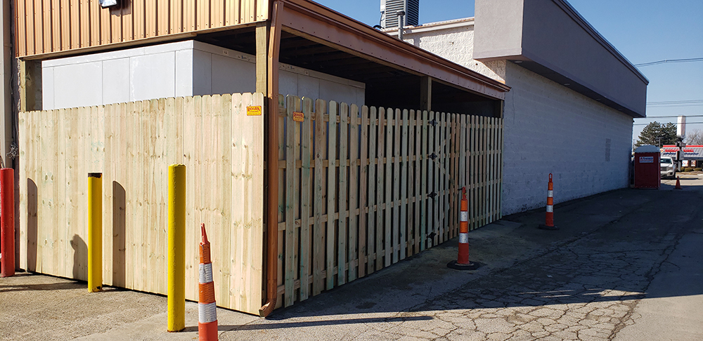 Wood privacy fence on a commercial property completed by Roark Fencing.
